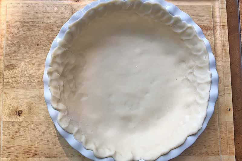 Vertical image of dough flattened in a white circular ceramic pan.