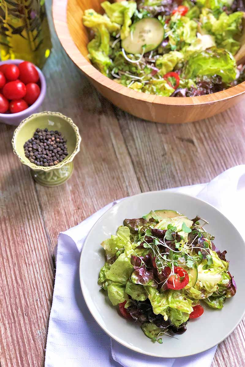 Vertical image of a plate and a wooden bowl of a salad mix on a wooden plate next to oil, a bowl of tomatoes, and a bowl of whole peppercorns.