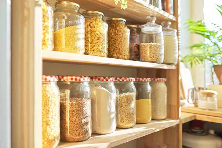 Horizontal image of shelves of yellow-themed dry goods in glass jars in a bright pantry.