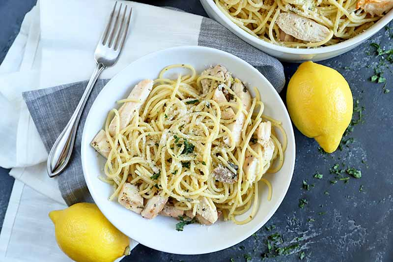 Overhead horizontal image of a white bowl and white serving dish of spaghetti with grilled poultry and minced herbs, on a gray surface with a folded white and gray cloth, a fork, and two yelow citrus fruits.