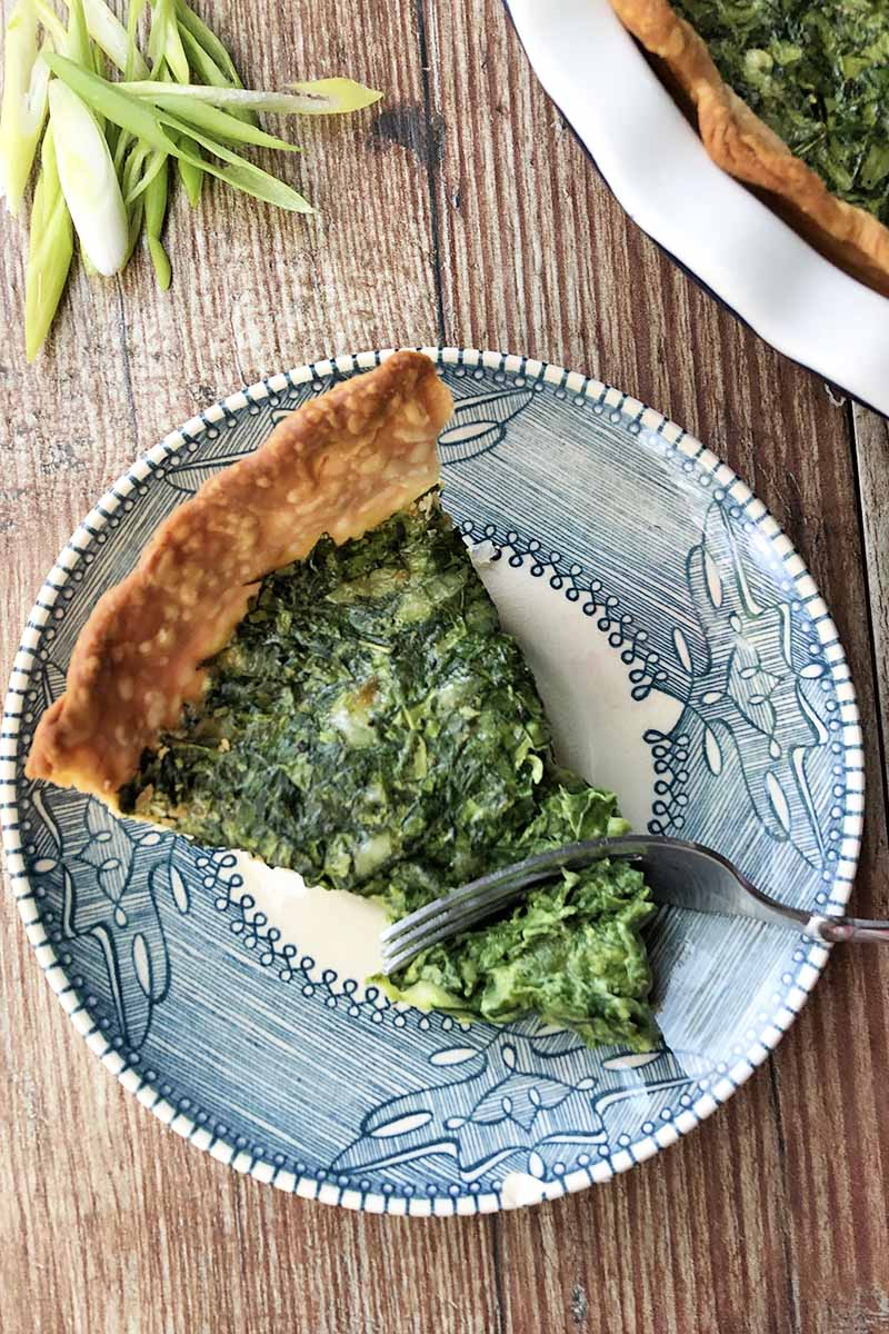 Vertical top-down image of a fork cutting into a slice of a quiche mixed with greens on a blue plate on a wooden table
