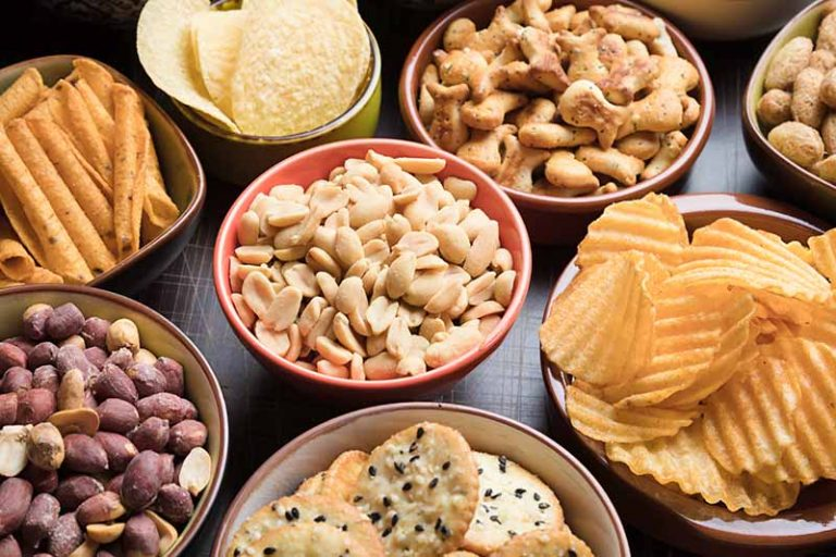 Horizontal image of bowls of various crunchy snack foods.
