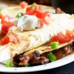 Horizontal image of a white plate with bean-stuffed tortillas in triangular shapes topped with tomatoes, sour cream, and scallions.