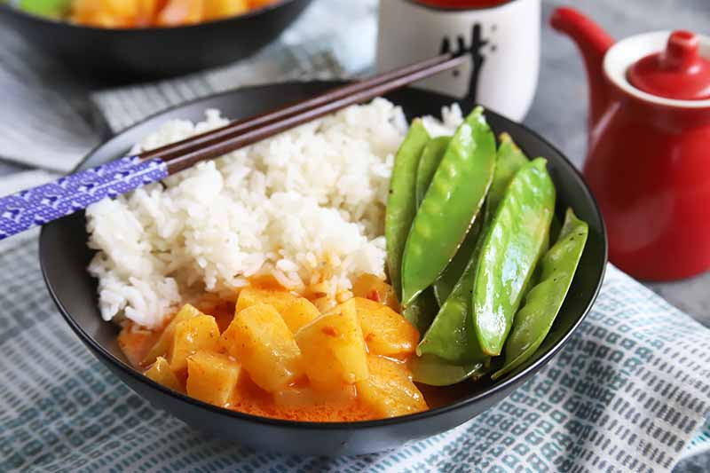 Horizontal image of a black bowl with fluffy white rice, oiled snap peas, and yellow fruit chunks in a light red creamy sauce, with chopsticks resting on the side of it, in front of cups on a checkered blue towel.