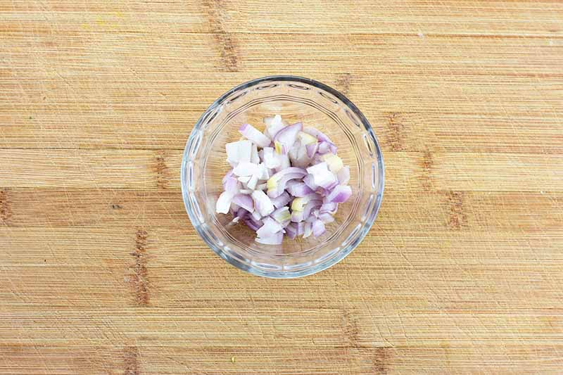 Horizontal image of a glass bowl with chopped shallots on a wooden cutting board.