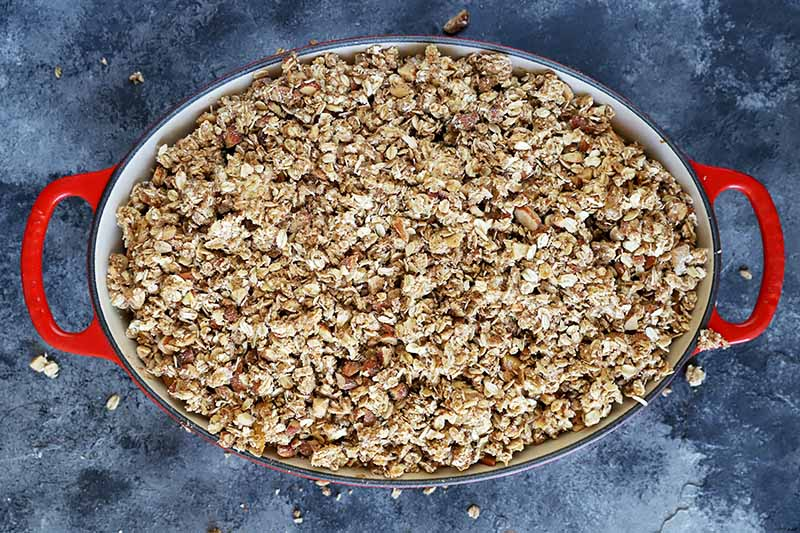 Horizontal top-down image of an oval baking dish with red handles with an oat and nut mixture spread on top.