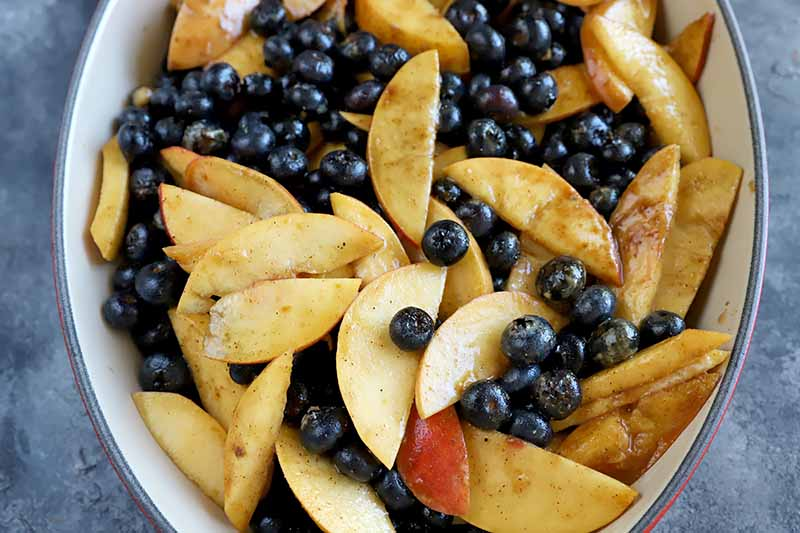 Horizontal image of an oval baking dish with a seasoned mixture of blueberries and sliced peaches.