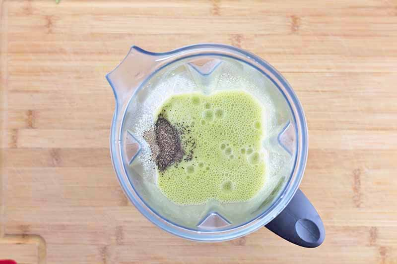 Horizontal image of a blended green liquid and a mound of seasonings in a blender.
