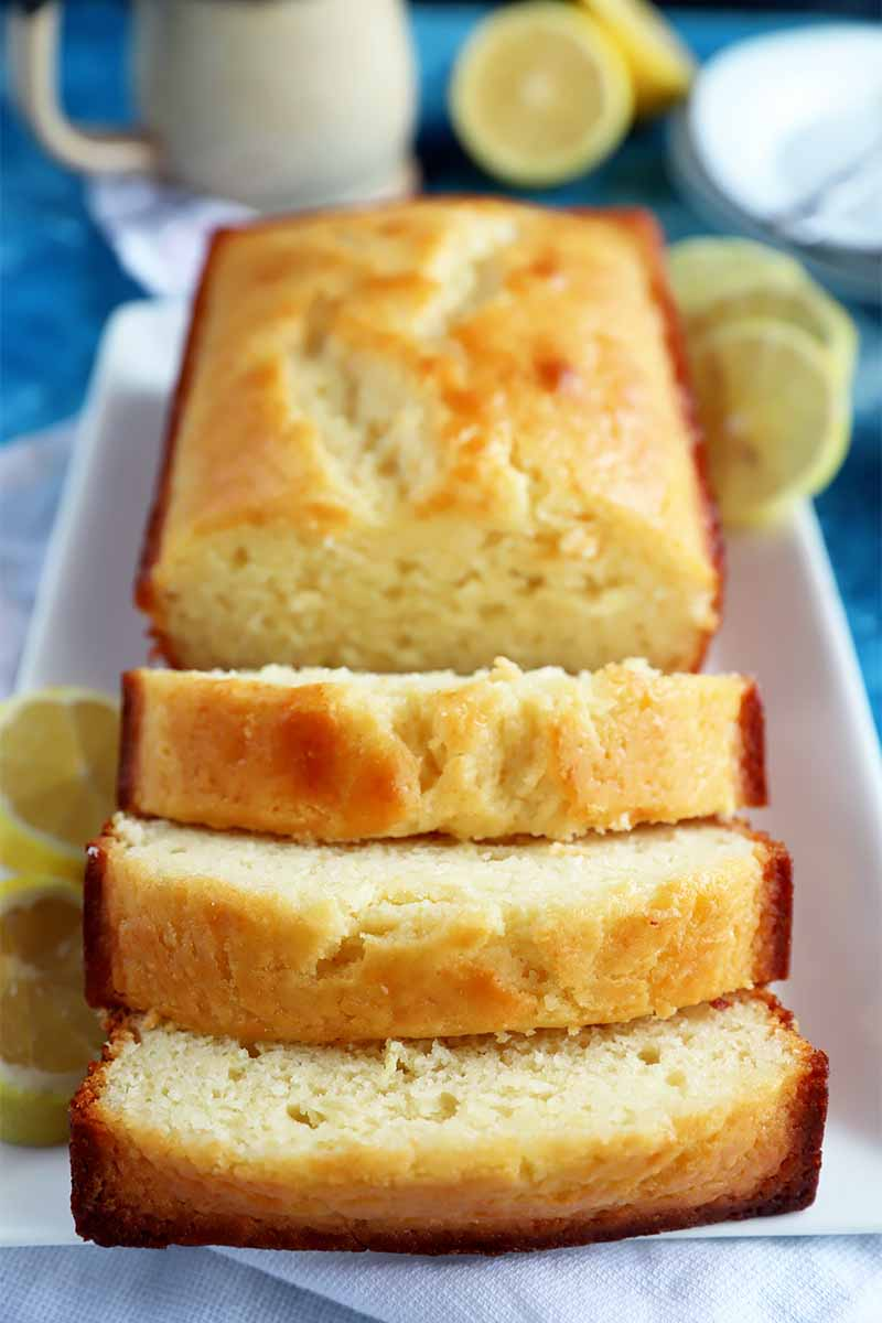 Vertical image of a loaf cake with three slices on a rectangular white plate in front of a mug and lemon wedges.