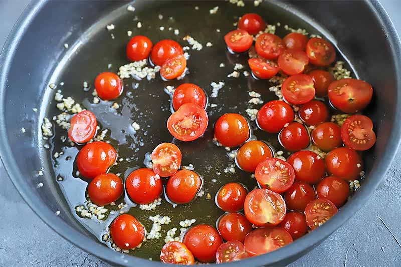 Horizontal image of sliced grape tomatoes cooking in an oiled pan.
