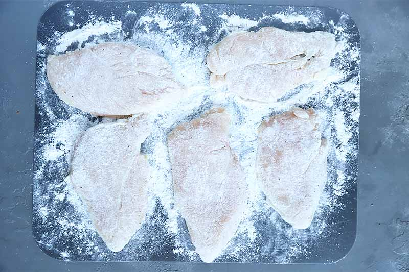 Horizontal image of dredged poultry slices on a black cutting board.