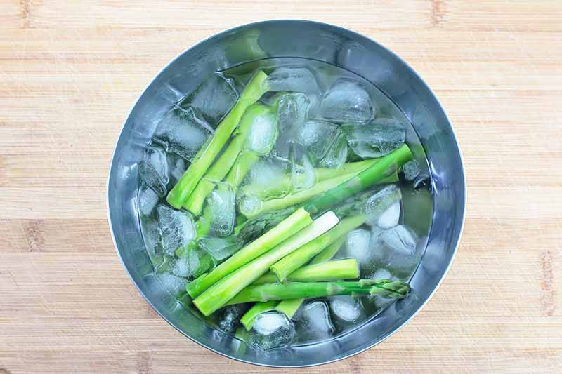 Horizontal image of cooked green stalks in a bowl with ice.