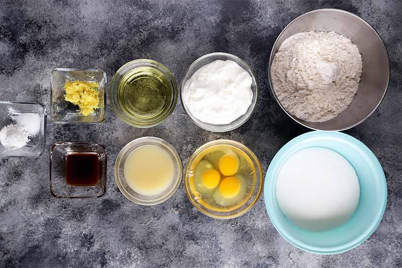 Horizontal top-down image of assorted wet and dry ingredients in glass bowls on a gray surface.
