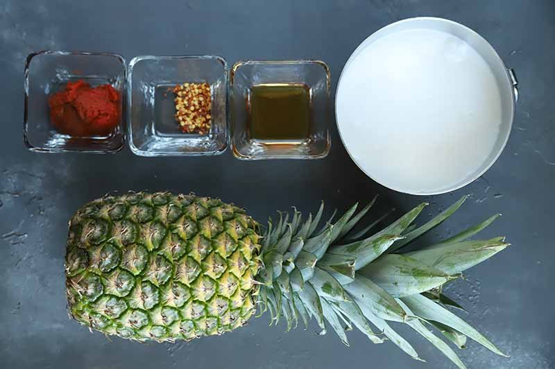 Horizontal image of a whole pineapple, three small glass dishes with assorted seasonings, and a white bowl with coconut cream on a black surface.