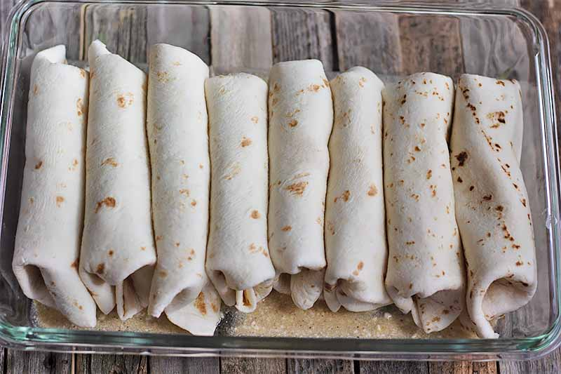 Horizontal image of stuffed and rolled soft tortillas in a neat row in a glass casserole dish on a wooden table.