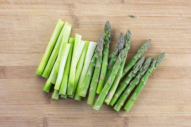 Horizontal image of prepped asparagus on a wooden board.