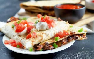 Horizontal image of a plate of quesadilla cut in wedges with tomato, sour cream, and scallion garnish.