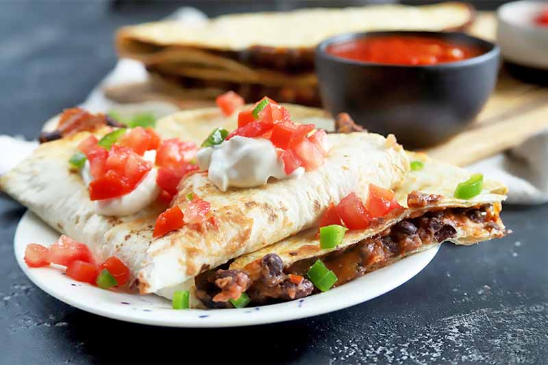 Horizontal image of a pile of triangular tortillas stuffed with a bean mixture garnished with diced tomatoes and white sour cream on a white plate.