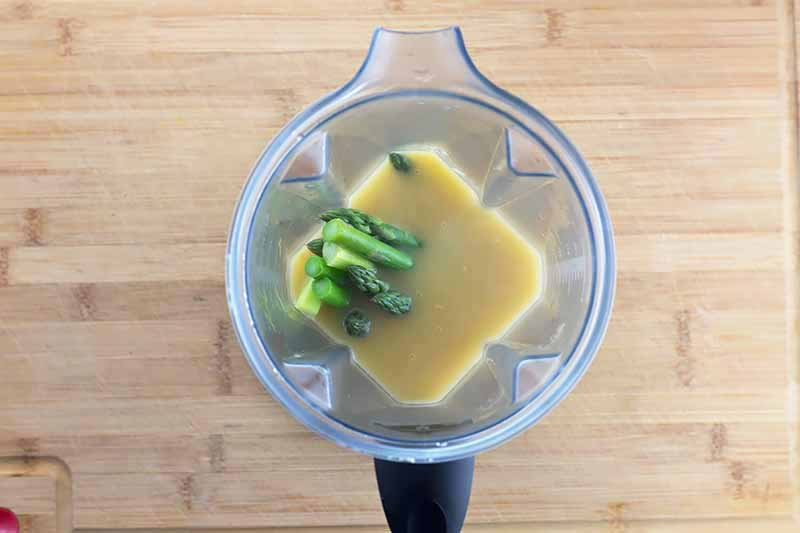Horizontal image of a blender with green vegetable stalks and a brown liquid on a wooden cutting board.