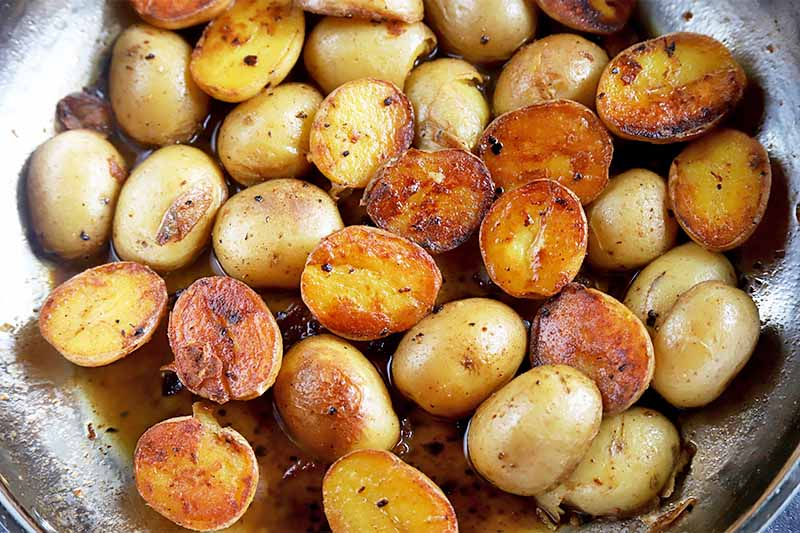 Horizontal image of a pan with oil and browned small spuds cut in half.