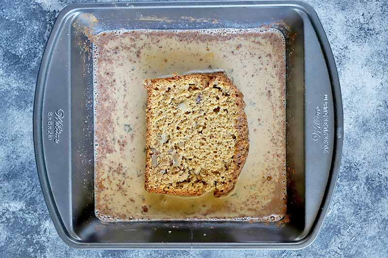 Horizontal image of a square pan with a milk and spice mixture with a piece of sliced bread soaking in it.