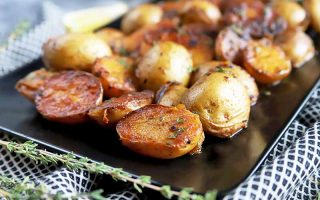 Horizontal image of cooked small potatoes on a black plate on a white and black towel next to fresh herbs.
