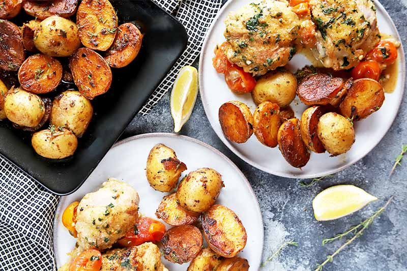Horizontal image of two plates with chicken, potatoes, and tomatoes next to a black plate with more potatoes on a towel next to lemon wedges and fresh herbs sprigs.