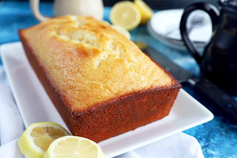 Horizontal image of a whole loaf cake on a white plate next to lemon slices on a blue surface.