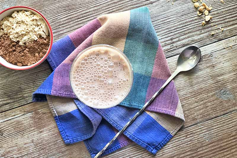 Horizontal top-down image of a cup with a frothy milk on a colorful towel nest to a spoon, chopped nuts, and powdered ingredients in a bowl.