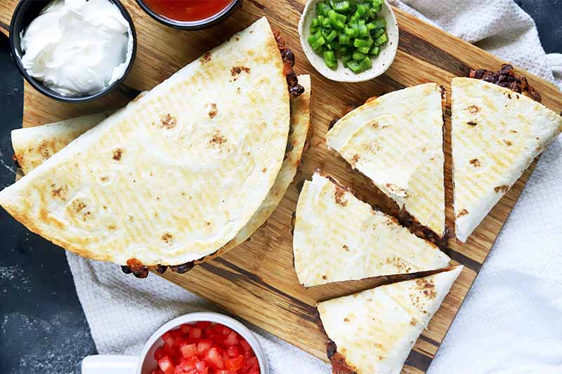Horizontal image of whole folded quesadillas and triangular-cut pieces surrounded by bowls of tomatoes, sliced scallions, salsa, and sour cream, all on a wooden cutting board