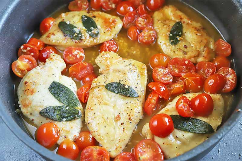 Horizontal image of a pan with poultry topped with herbs and tomatoes in a light liquid.