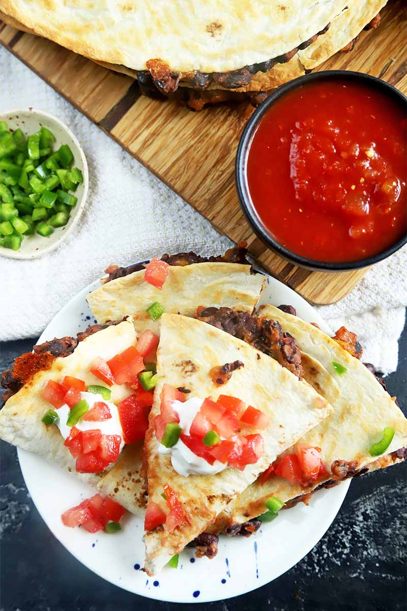 Vertical top-down image of a pile of triangular stuffed soft tortillas on a white plate garnished with diced tomatoes, sour cream, and scallions next to a bowl of red salsa and a bowl of sliced scallions on a wooden cutting board on a white towel.