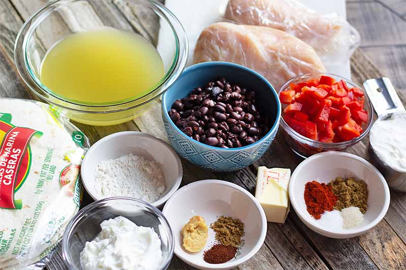 Horizontal image of a gathering of ingredients on a wooden table: spices in small white bowls, black beans in a blue bowl, melted butter in a glass bowl, chopped red peppers in a white bowl, a slice of butter, uncooked chicken breasts, and a bag of soft tortillas.