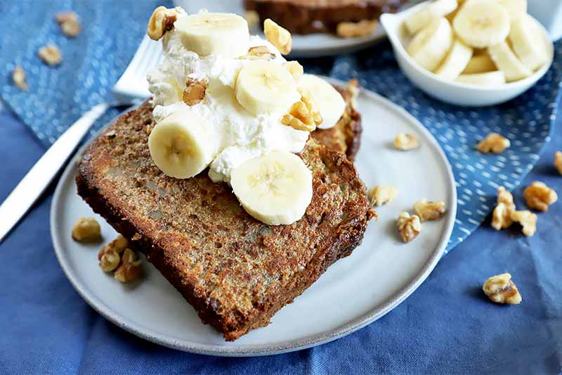 Horizontal image of white plates with two slices of bread each topped with whipped cream, bananas, and nuts on a blue tablecloth.