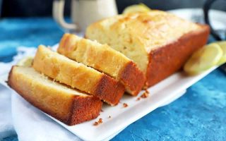 Horizontal image of a loaf baked good sliced into thick pieces on a white plate on a bright blue surface.