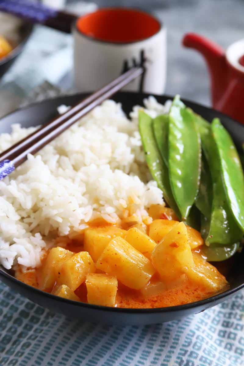 Vertical image of white rice, chopped pineapple in a light red sauce, and snap peas in a black bowl with chopsticks in front of cups on a blue checkered towel.