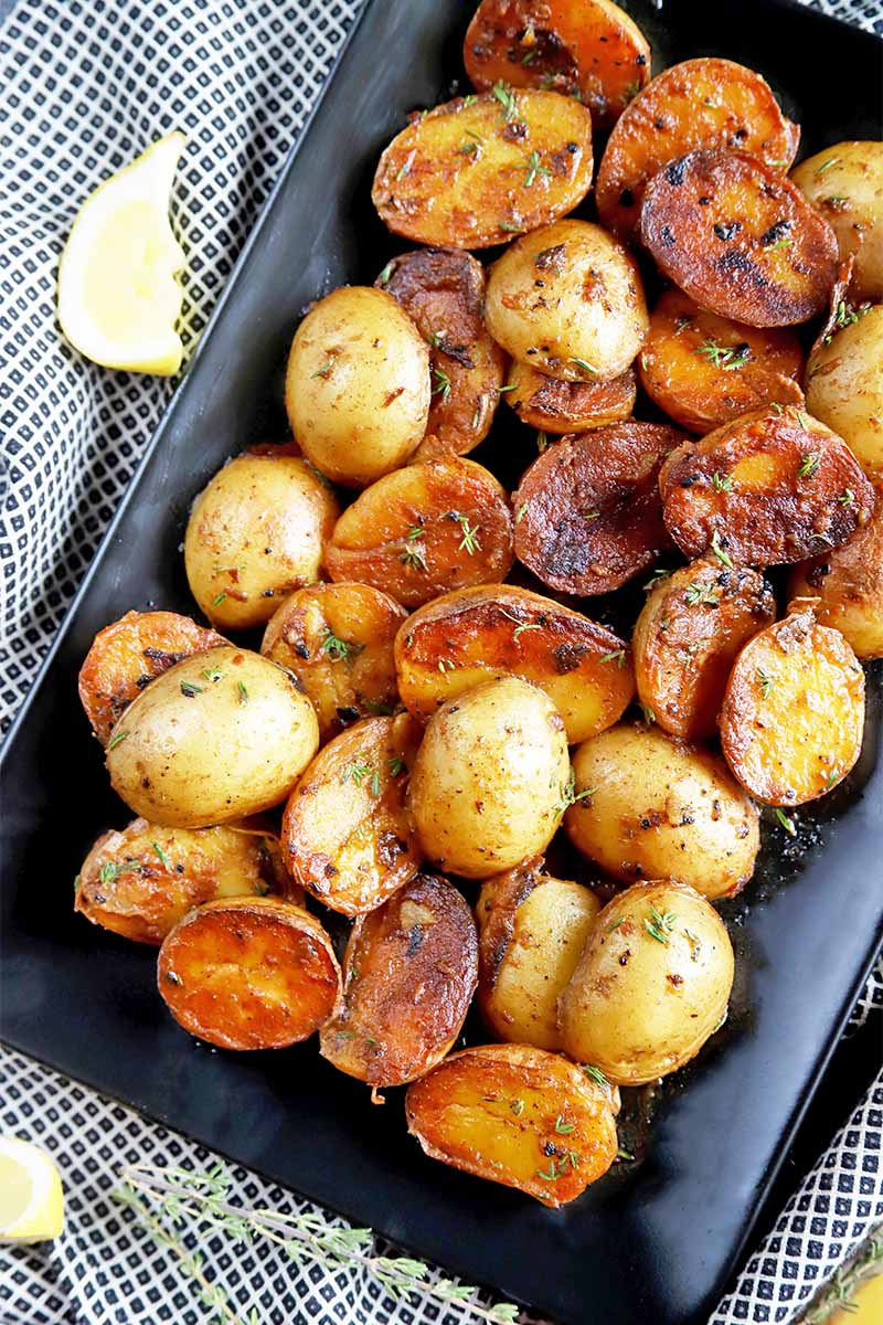 Vertical top-down image of a black plate with browned small potatoes with seasonings on a black and white towel next to herbs and lemon wedges.