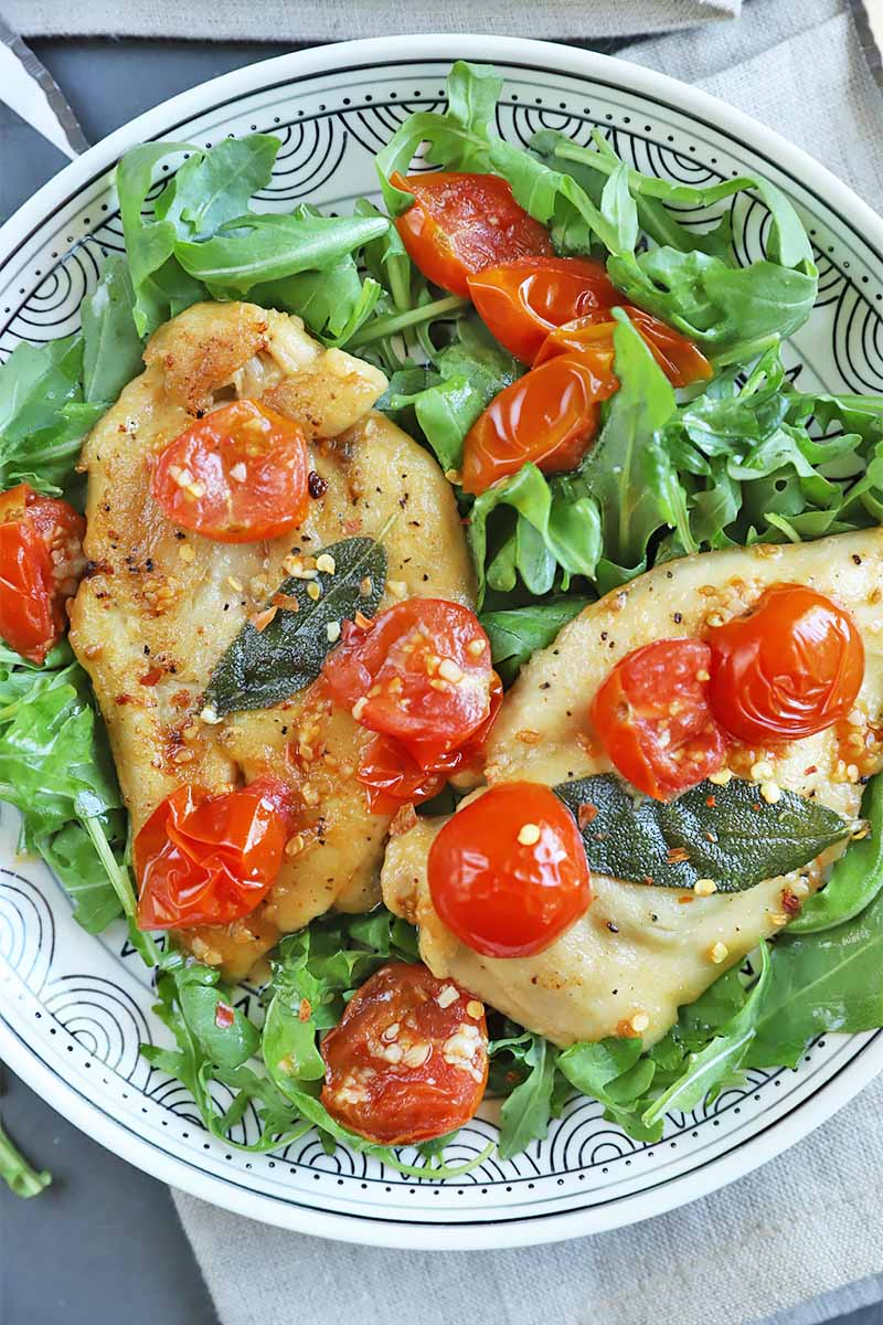 Vertical close-up image of a plate with two poultry breasts topped with tomatoes over a bed of greens.
