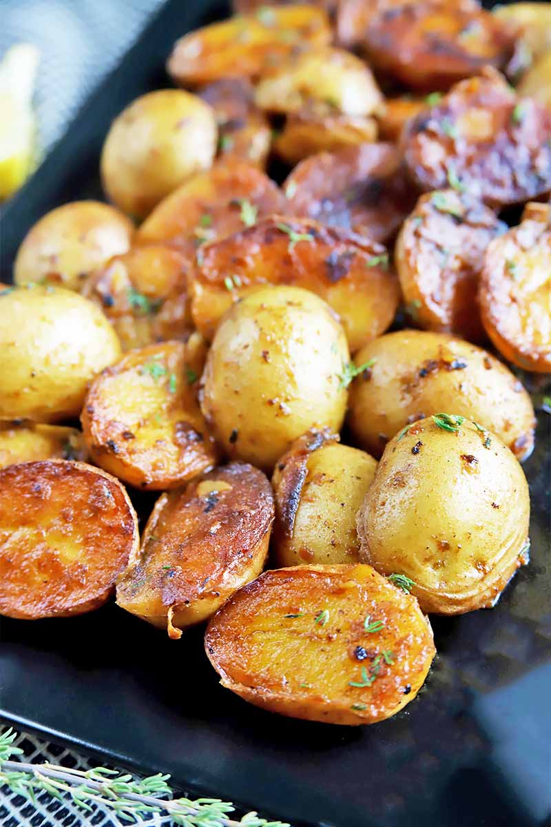 Vertical image of a black tray of browned baby spuds with seasonings.