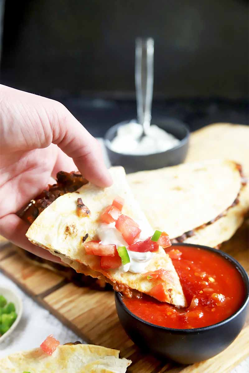 Vertical image of a hand dipping a wedge of quesadilla garnished with diced tomatoes, sour cream, and scallions in a black bowl of salsa on a wooden cutting board, with a black bowl of sour cream in the background of a black backdrop.