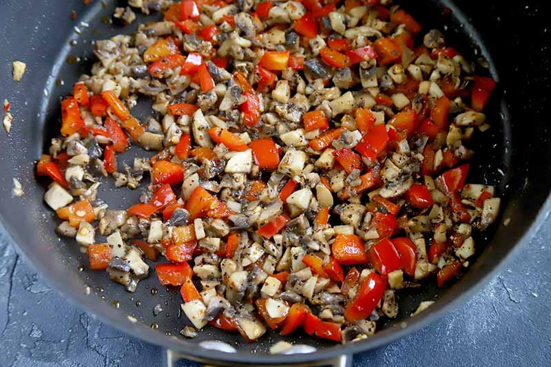 Horizontal image of finely chopped and cooked mushrooms and peppers in a pan.