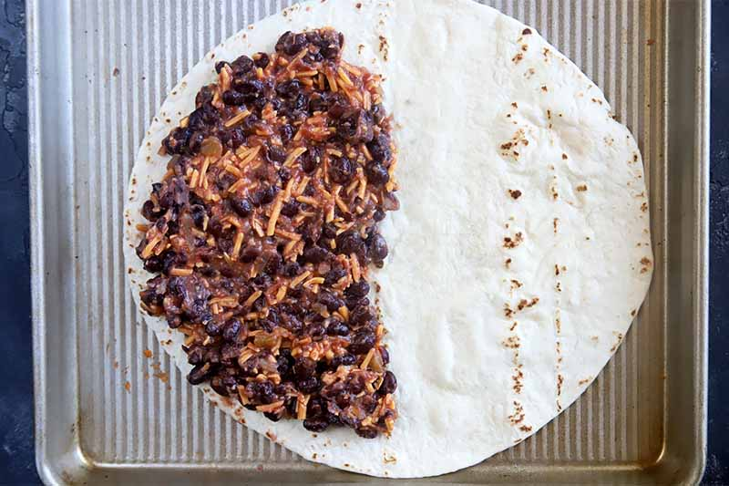 Horizontal image of a flour tortilla with a bean and cheese mixture spread on half of it on a baking sheet.