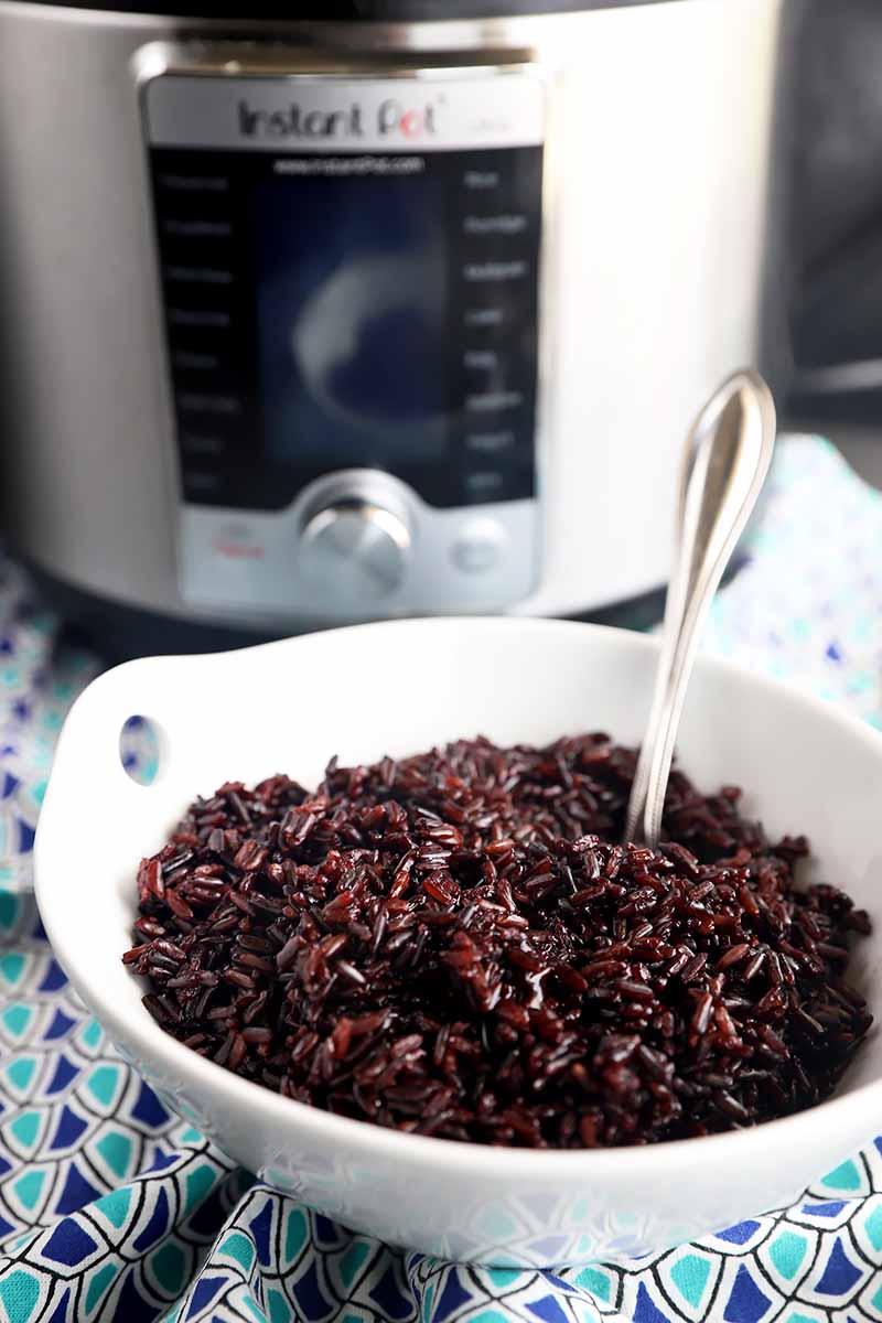 Vertical image of black rice in a white bowl with a metal spoon in front of an Instant Pot on a blue patterned napkin.