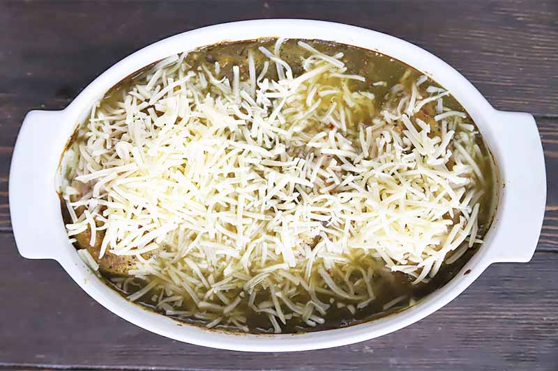Horizontal image of a white casserole dish filled with meat covered in a green sauce and shredded white cheese on a dark surface.