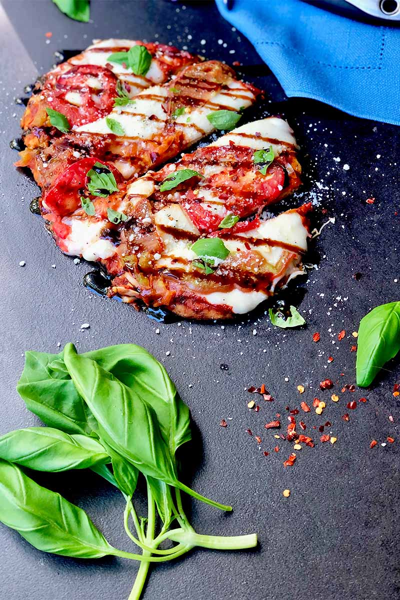 Vertical image of a pizza drizzled with balsamic glaze and topped with basil on a dark counter, next to a blue towel, whole basil leaves and red pepper flakes.