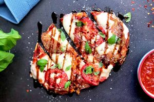 Horizontal top-down image of a Caprese flatbread on a dark surface next to a blue towel, basil, and marinara in a bowl.