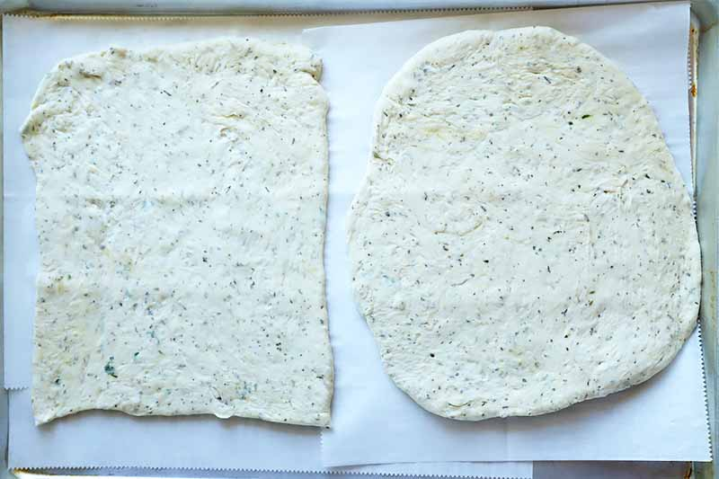 Horizontal image of a square and a circle shape of an unbaked dough studded with fresh herbs on a parchment paper.