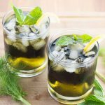 Horizontal image of two glasses with a green liquid topped with ice, mint, and lemon next to green fronds on a light wooden surface.