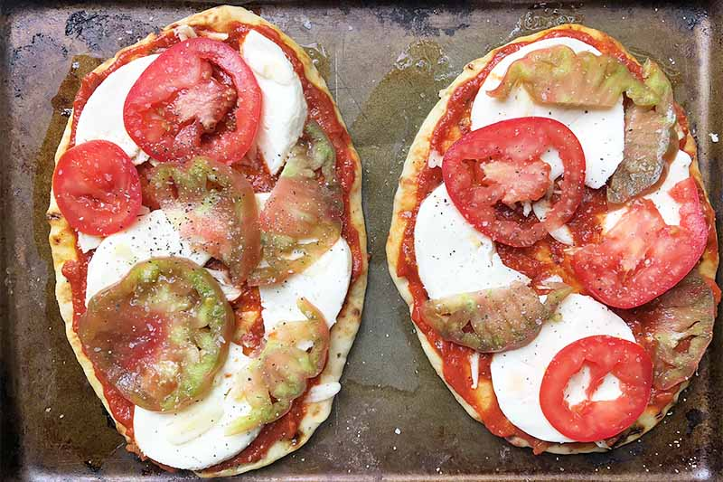 Horizontal top-down image of two naan topped with slices of mozzarella cheese and tomatoes.