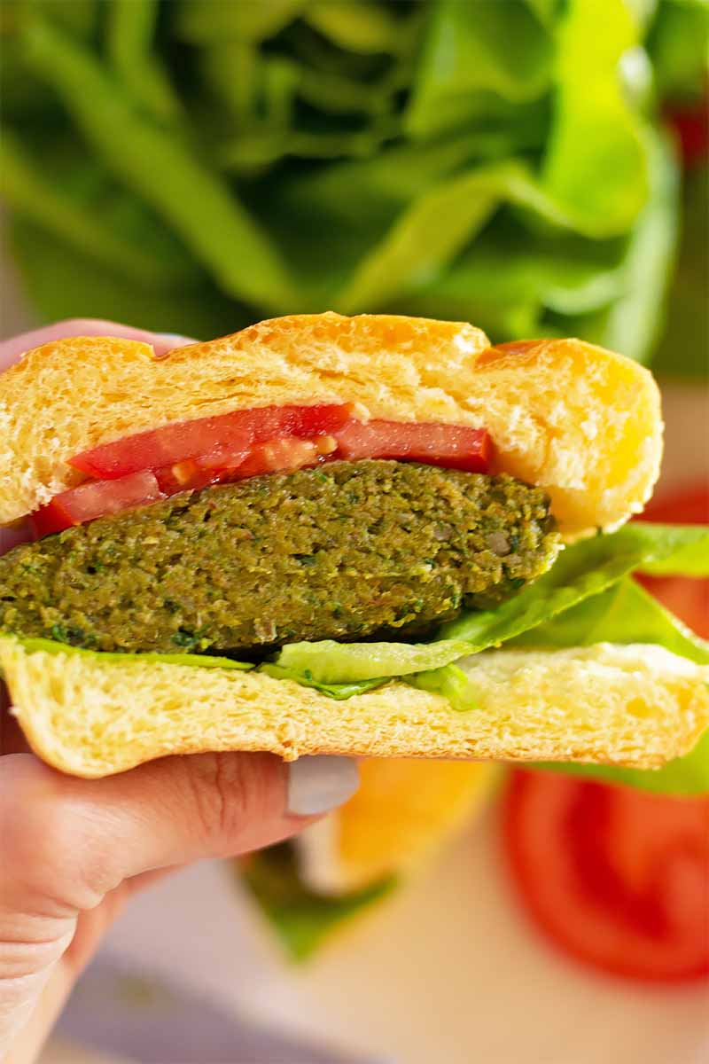 Vertical image of a hand holding half of a green veggie burger with lettuce and tomato.